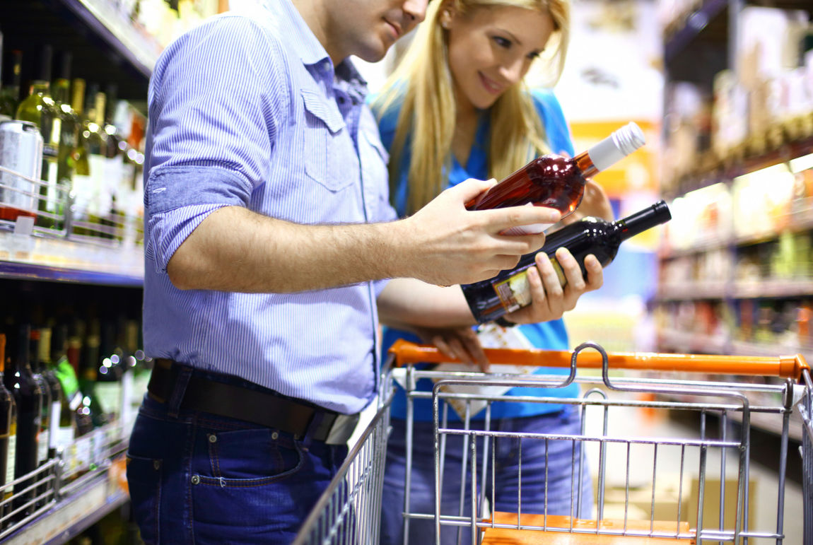 Couple buying wine in a supermarket