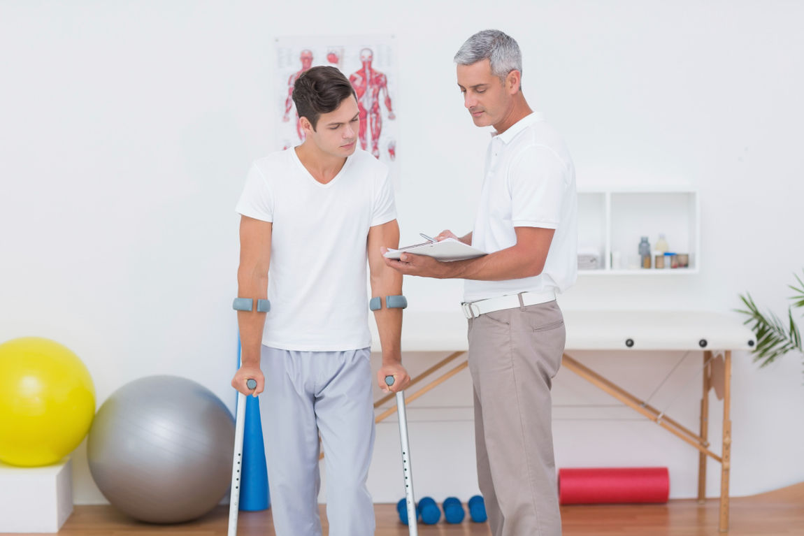Doctor showing clipboard to his patient with crutch
