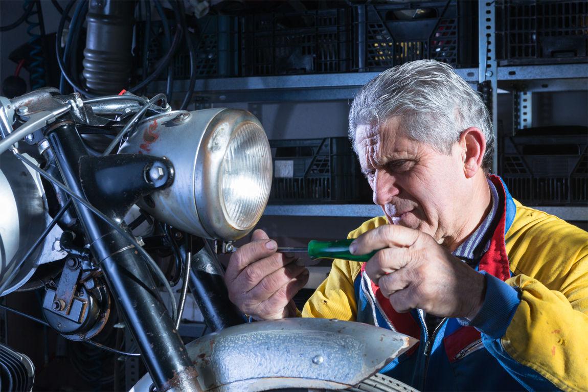 mechanic unscrewing the motorcycle headlight